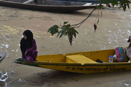 A Kashmiri girl crosses a flooded area with essential supplies on a boat