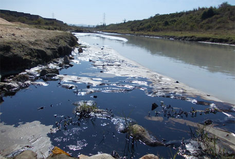 Patches of oil and ash in the Nalkari River