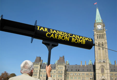 A protestor objecting to the continued expansion of the tar sands in front of Parliament Hill (Photo: Peter Blanchard)