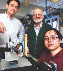 Researchers with the device that fingerprints melamine (Credit: PURDUE UNIVERSITY / ANDY HANCOCK))