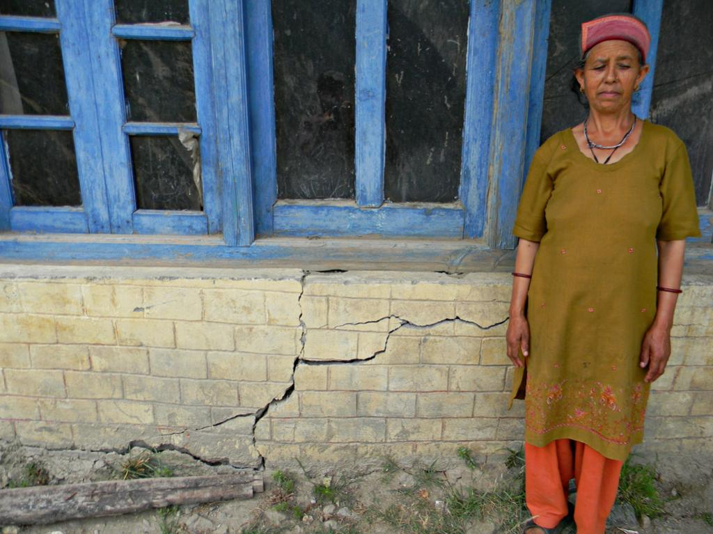 Kamla Devi distressed by the numerous cracks that have appeared in her house at Sudarang.