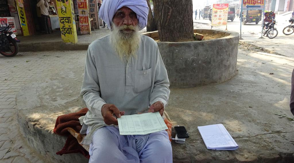 A farmer in front of bank, with his bank pass books showing crop insurance premium deduction from their bank accounts without his consent (Credit: Vineet Kumar/CSE)