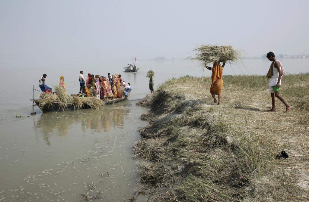 People carry bundles og grass on boats. Those living within the embankments have to depend on boats to go anywhere. Credit: Vikas Choudhary