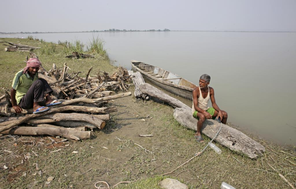 Logs that drift into the river from the Himalayan slopes in Nepal are collected by boatmen near the Kosi barrage. They are sold as fuelwood in nearby villages. Credit: Vikas Choudhary