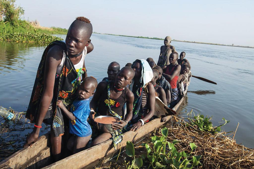 A group of women in a boat on the White Nile river in Terekeka, South Sudan. Here, FAO is distributing fishing kits to the local people. The kits enable fisherfolk to catch fish and feed their families. Each fishing kit provides enough capacity to feed 25 families for a day (Source: FAO/Albert Gonzalez Farran)