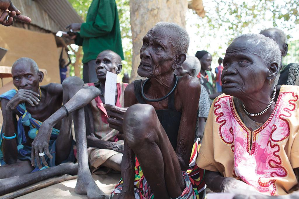 In South Sudan where famine has been declared, elderly women listen to news about possible assistance. Amid the worsening situation, vulnerable people queue up for food distribution programmes. Many of them are old and suffer from ill health. In Nyal, Pan