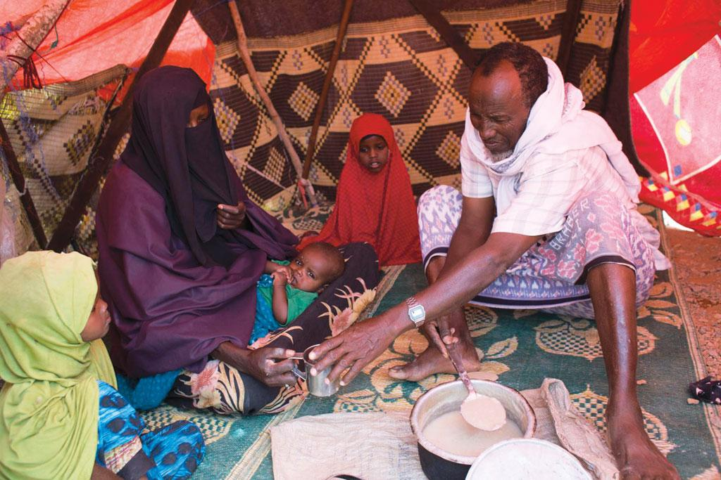 Muhamed Sharief Abdul eats lunch with his family inside their hut at a camp at Uusgure village in Somalia. Three consecutive poor rainfall seasons have reduced harvests in  the country (Source: FAO/Karel Prinsloo)