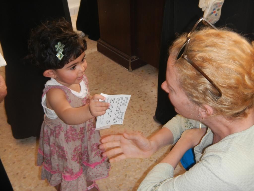 A toddler holding her immunisation card. Credit: CDC Global / Flickr