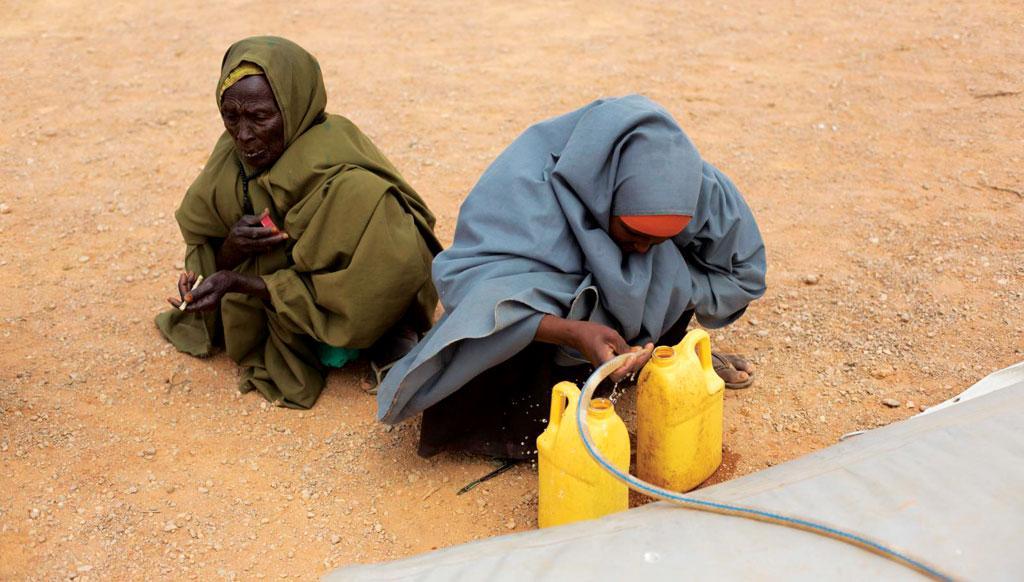 पंटलैंड, सोमालिया के उसुगेरे गांव में विस्थापितों  के शिविर में पानी की बोतल लिए अपनी बारी का इंतजार कर रही एक बुजुर्ग महिला (फोटो: एफएओ)