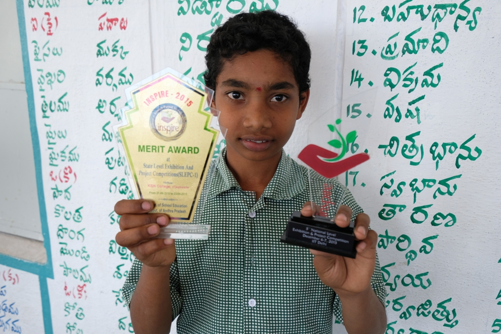 Naveen shows the prizes he won for the clean cooking invention (Credit: CRY)