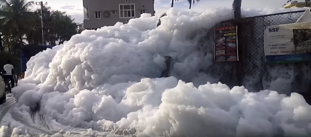 Froth from the lake covers the road in Bengaluru (Credit: Rohit Saxena/YouTube)