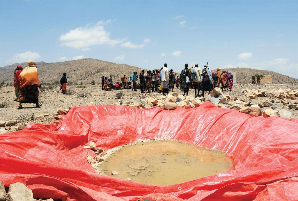 Displaced people gather at an artificial water pan near Habaas town of Awdal