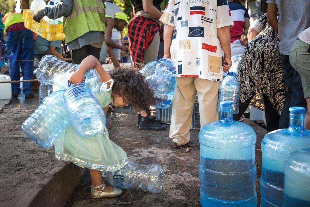 Capetonians wait for their turn at a natural spring with bottles 
