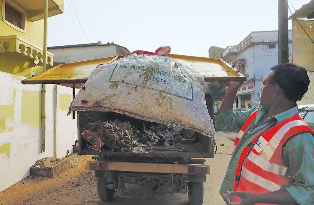 Waste collectors in Balaghat tie a gunny bag behind the truck to segregate plastic waste on a daily basis