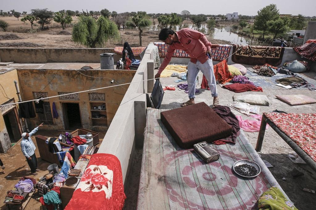 A man keeps things on his terrace to dry after the storage tank of the dam, which contained 4,400 million litres, burst and two-thirds of the water entered houses and shops in the area