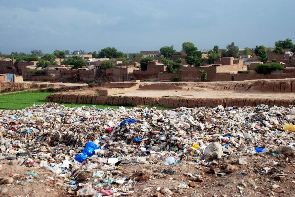 A view of solid waste near the populated area of Aftab Abad in Peshawar. Besides creating nuisance and a bad stink for locals, the leachate produced from the dump also affects agricultural land. Credit: Adeel Saeed
