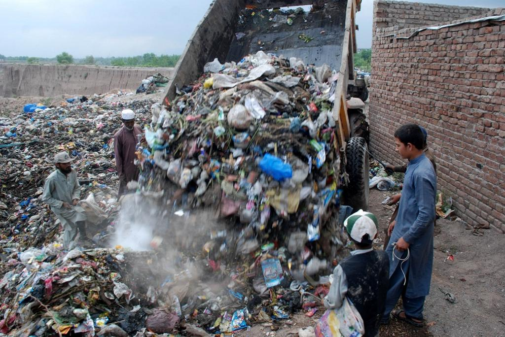 Scavengers gather as a rubbish-laden vehicle is unloaded at new solid waste dumping site in Peshawar, quite far away from populated areas. Credit: Adeel Saeed