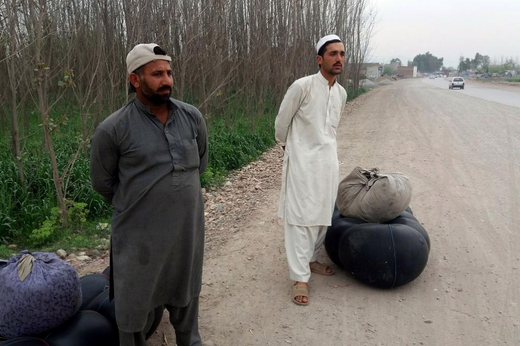Two fishermen along with their gadgets including inflated plastic tube and net waiting for public transport on the outskirts of Peshawar to travel to Michni and fish for Sher Mahi. Credit: Adeel Saeed