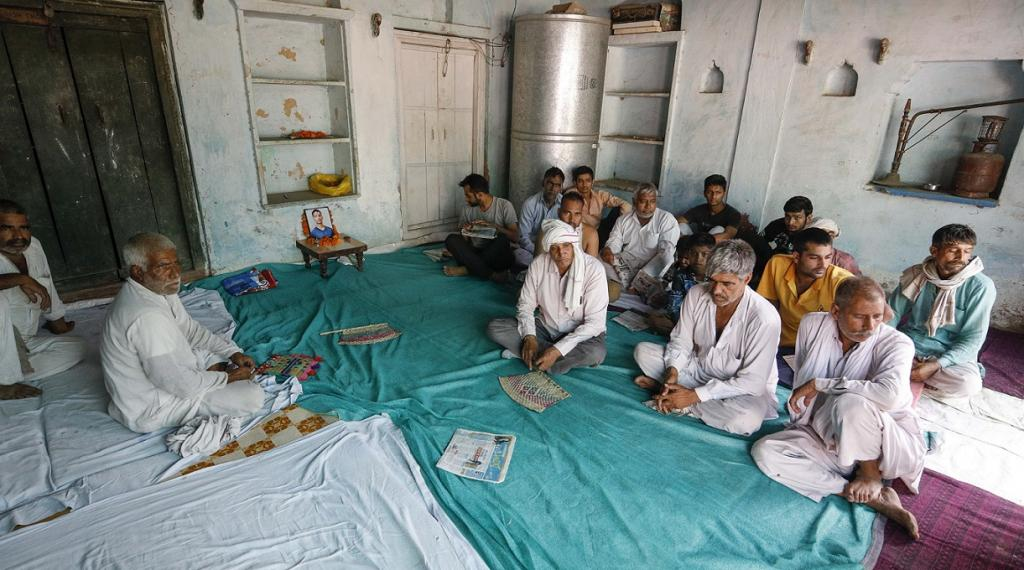 Father of Chandravir (second form the right) and his neighbours with the photo of the 20-year-old who died on May 2. Credit: Vikas Choudhary