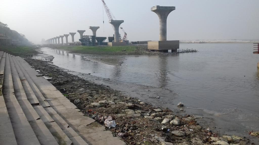 Both the garbage and the pillars of the Ganga Pathway, are blocking the clear flow of water. Credit: Mohd Imran Khan