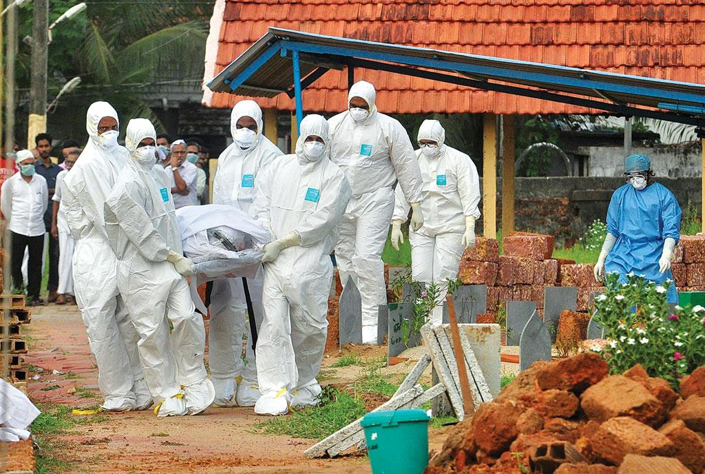 Doctors and relatives wearing protective gear carry the body of a Nipah virus victim, who died on May 24, at a burial ground in Kozhikode, Kerala (Photo: Reuters)