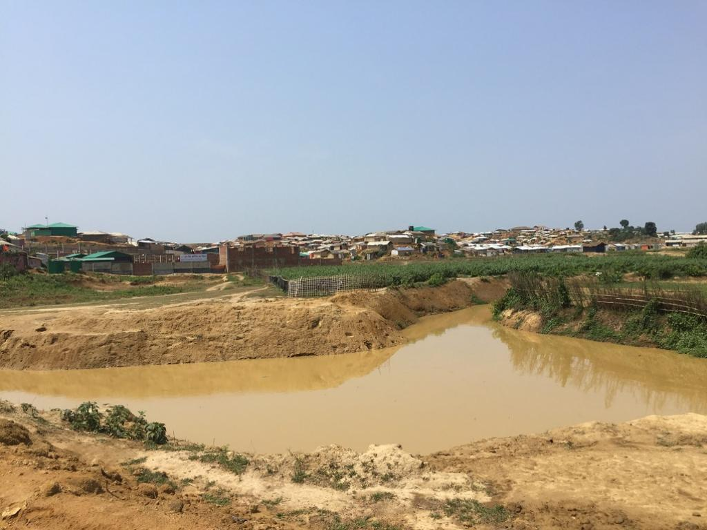 A pond has become contaminated as heavy rainfall has led to sewage and waste flooding into it. Credit: Mohammad Al-Masum Molla