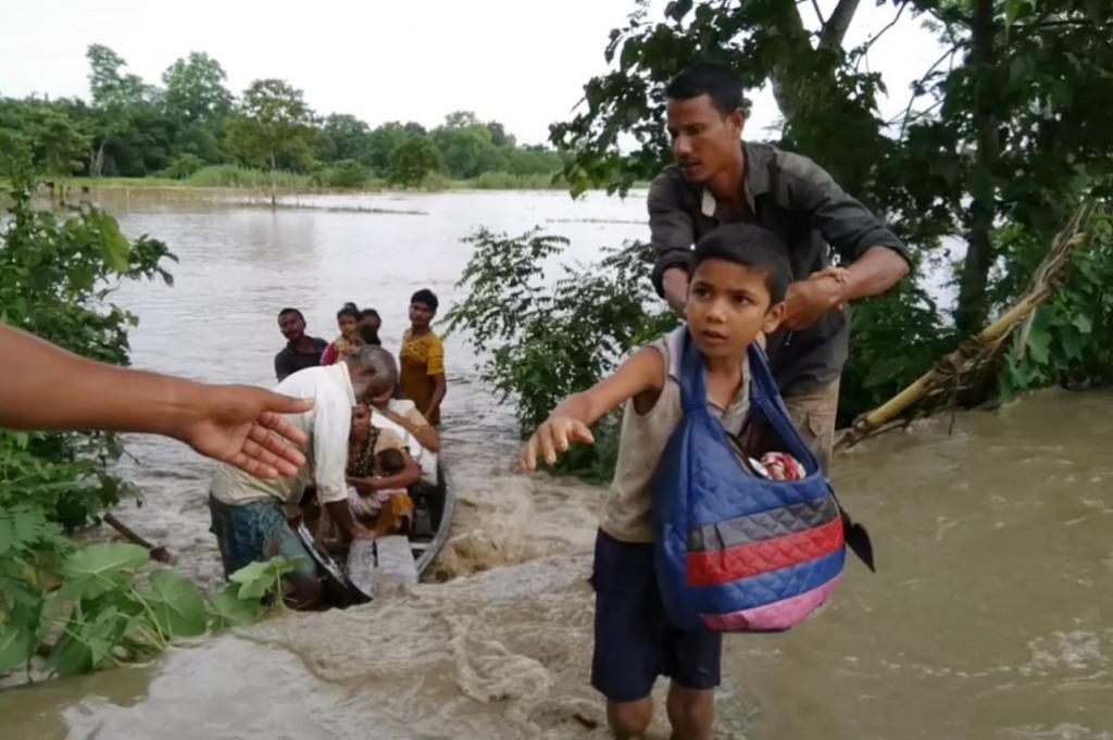 A boy tries to save his schoolbooks as the Dhansiri river floods its banks in Assam. Credit: Rubul Ahmed