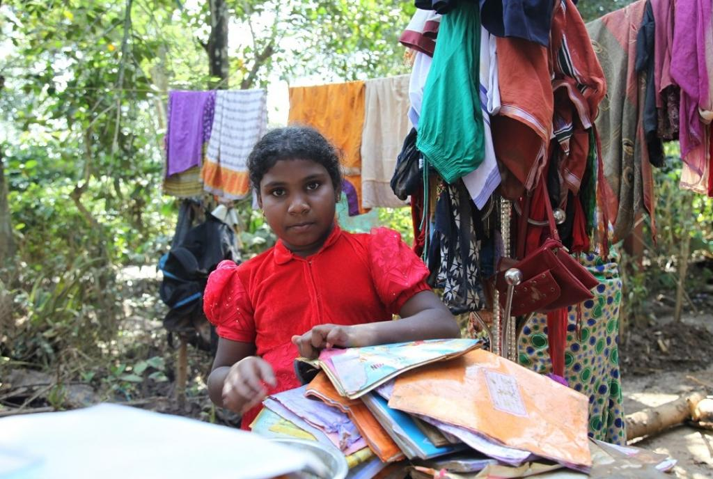 """I have no bag, books or uniform left to take to school once it re-opens after Onam holidays,"" says Sunisha who is in the fourth grade. She was trying to dry her damp books. The flood waters came with no warning and she could not take along any of her books, as her family ran for life. ""There is no electricity and we don't even have any firewood left to cook food,"" says Ambili, Sunisha's mother"