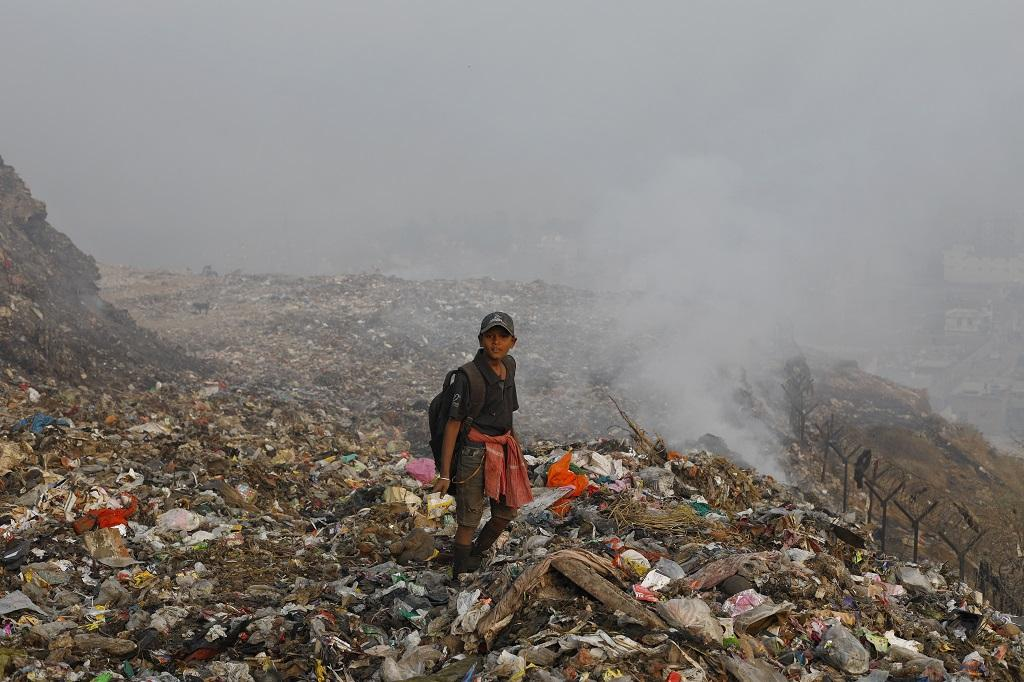 Sahibe Alam, 12, goes to school in the evening and works in the dumpyard during the day to earn Rs 100-200 to help his mother to run the household. Alam says the smoke makes it extremely difficult to work here. Credit: Vikas Choudhary