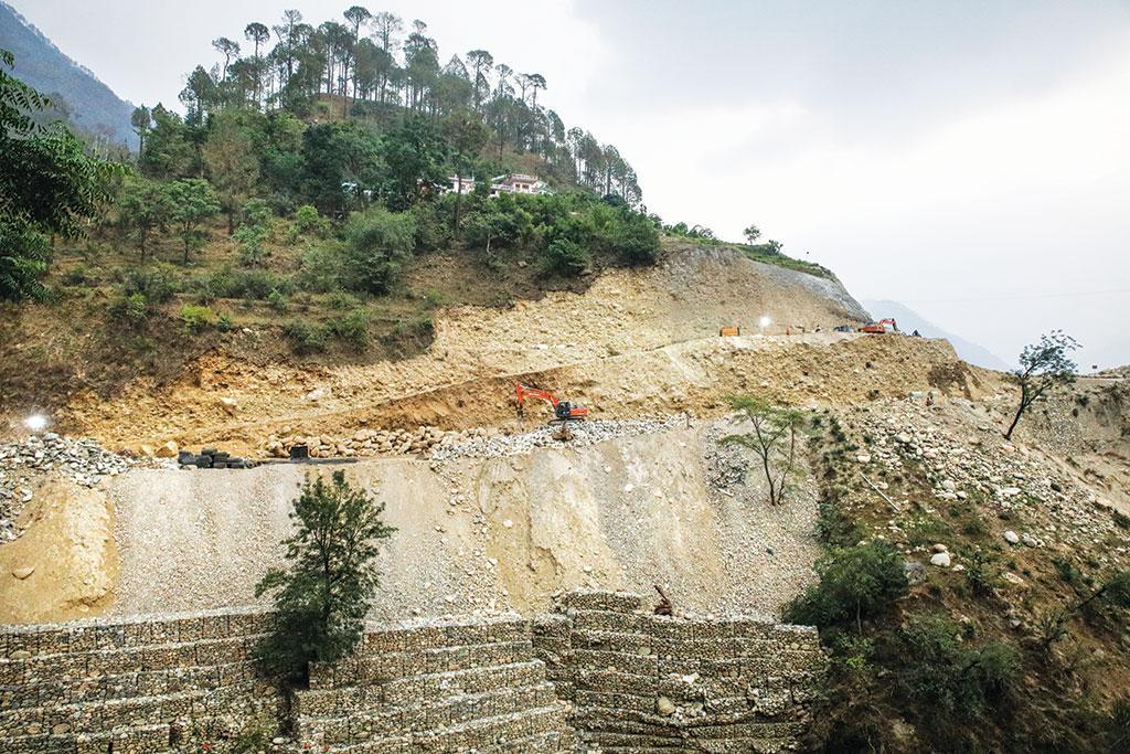 पहाड़ को थामने के लिए बनाई गई कंक्रीट की दीवार यहां कामयाब नहीं है। कीचड़ और छोटे बड़े पत्थर के टुकड़े अक्सर सड़क पर गिर जाते हैं  (फोटोग्राफर विकास चौधरी)