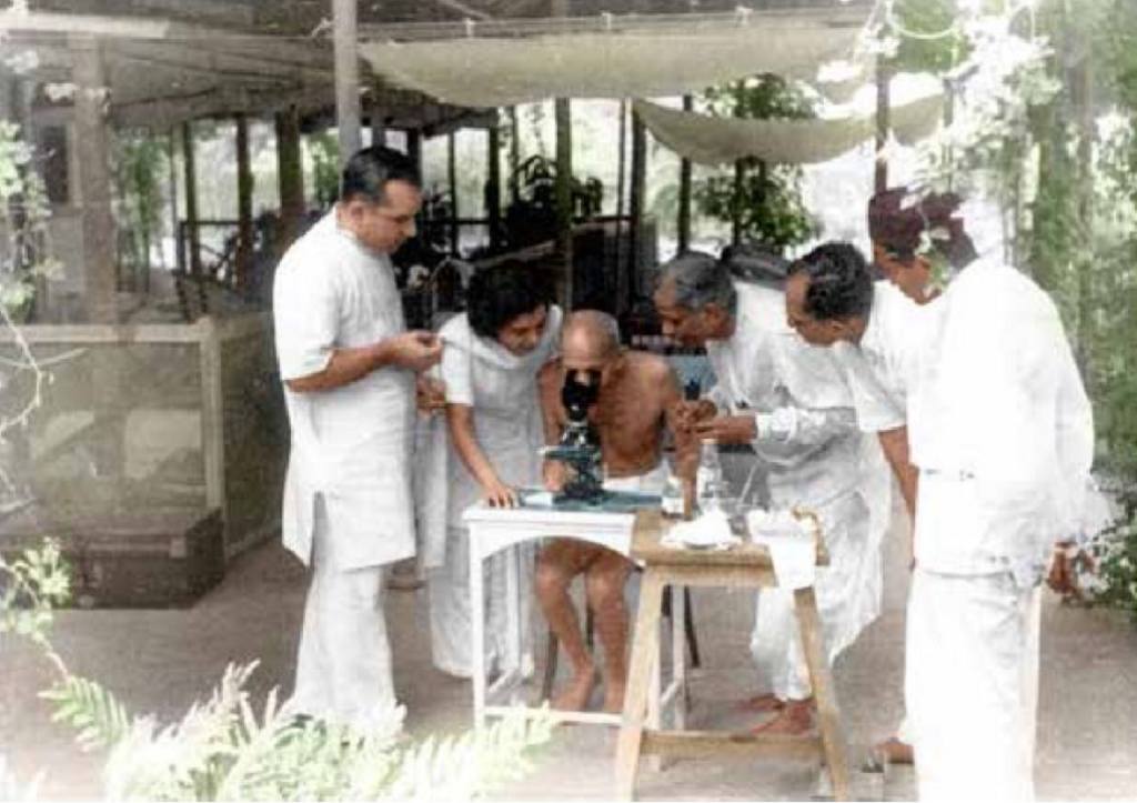Doctors showing Mahatma Gandhi hookworm ova under microscope in Mumbai, May 1944. Photo: IJMR