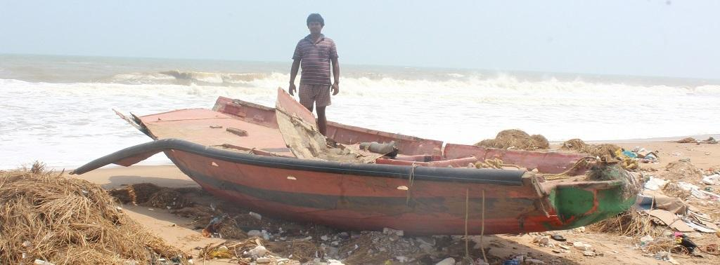 A fisherman stands near his damaged boat in Penthakata village. Photo: Ashis Senapati
