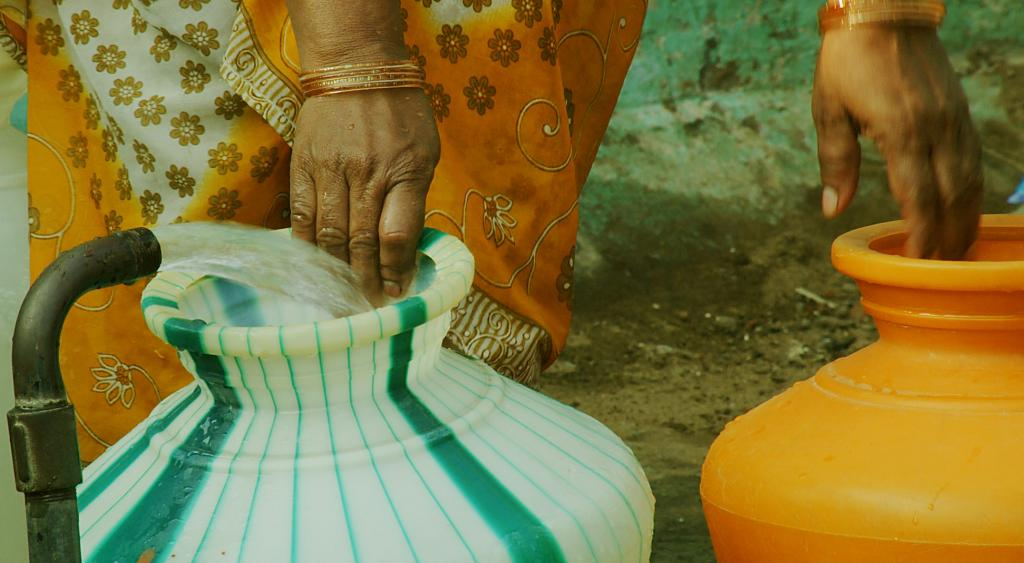 A rural woman fills vessels with water. Photo: Getty Images