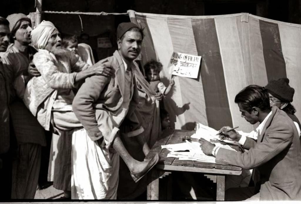 A man carries his visually challenged man to a polling booth in Jama Masjid area in Delhi during the 1951 Lok Sabha elections. Photo: Wikimedia Commons