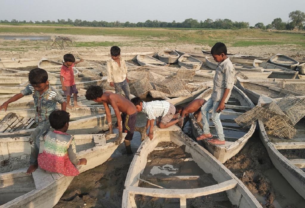 नदी सूखने के बाद खड़ी नावों में खेलते बच्चे। फोटो: पुष्यमित्र