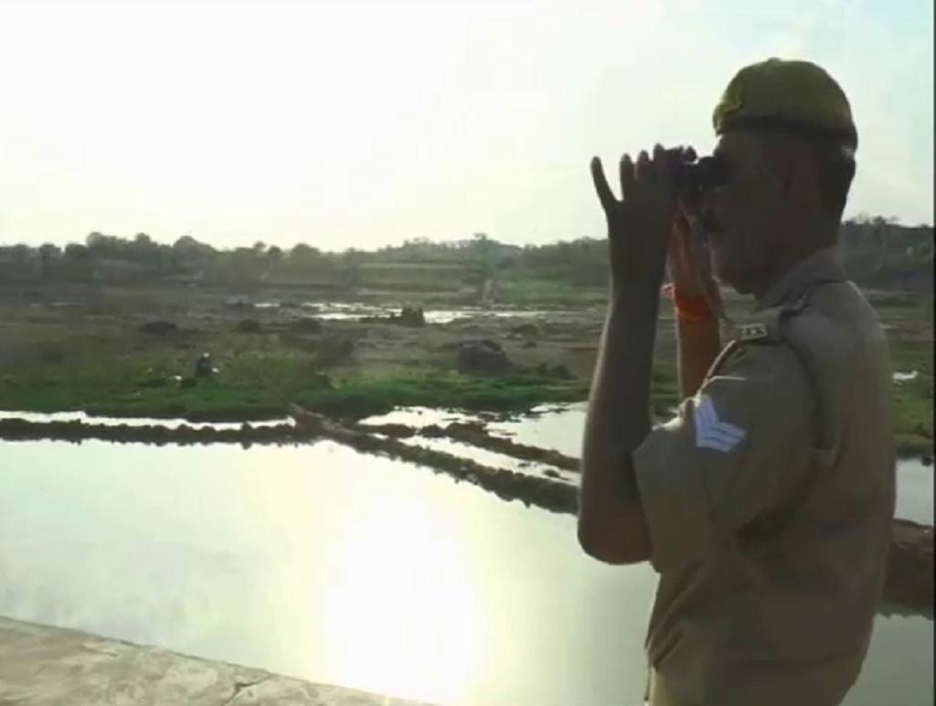 केन नदी पर दूरबीन से पहरेदारी करता पुलिस कर्मी। फोटो: प्रियंका पांडे