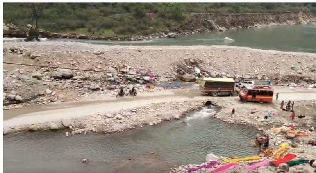 मंदाकिनी नदी पर मलबा डाल कर बनाई गई सड़क से गुजरते वाहन। फोटो: त्रिलोचन भट्ट