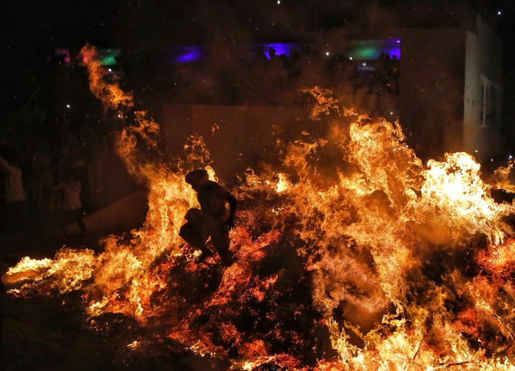 Babulal, a priest, runs through fire during a ritual on Holi in Phalen village near Mathura. Photo: Vikas Choudhary