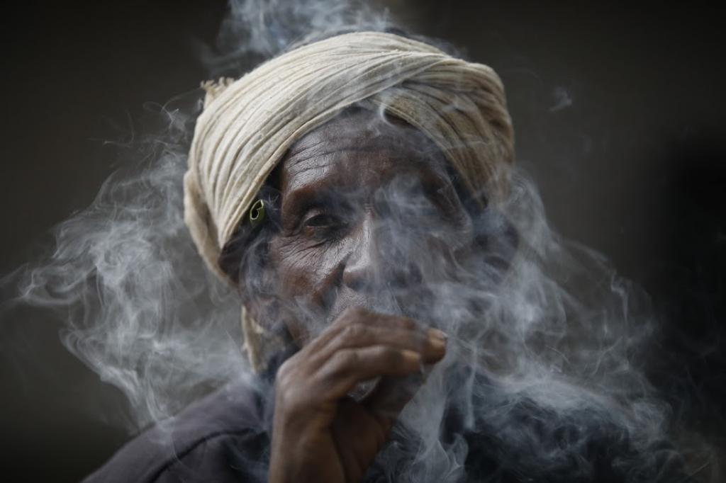 A Baiga tribesman smokes a bidi he made. He has filled a sal tree leaf (Sarai patta) with unprocessed tobacco. Baigas were among the first forest dwelling communities to gain habitat rights. Many such communities now fear that the cover provided to them by the Forest Rights Act may not stand long. Photo: Vikas Choudhary
