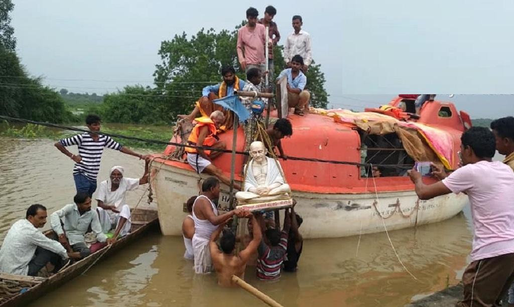 सरदार सरोवर बांध का जलस्तर बढ़ने के कारण डूब चुके गांव चिखल्दा से महात्मा गांधी की मूर्ति को हटाते नर्मदा बचाओ आंदोलन के कार्यकर्ता। फोटो- रहमत