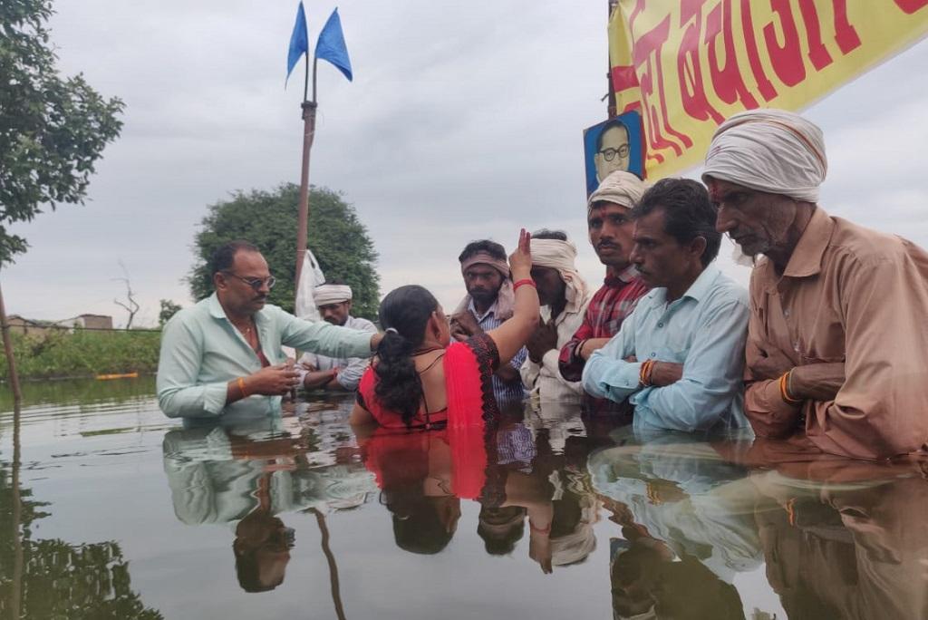 पानी में खड़े होकर ओंकारेश्वर बांध का विरोध कर रहे आंदोलनकारियों को उनकी बहनों ने पानी में घुसकर भैया दूज मनाया। फोटो: एनबीए