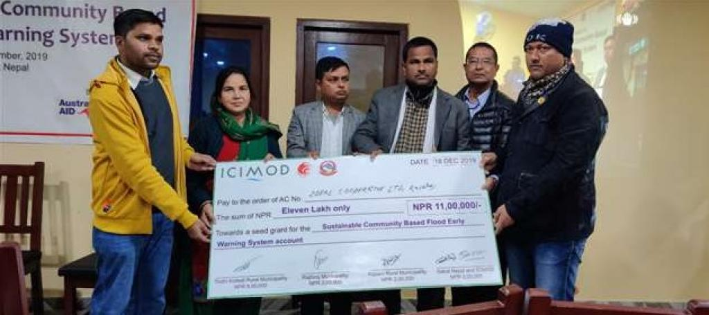Representatives from three rural municipalities along with Arun Bhakta Shrestha (ICIMOD, second from right) hand over a cheque to the local cooperative Photo: ICIMOD