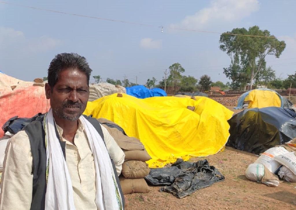 मध्यप्रदेश, रीवा जिले के दुआरी गांव में अपने धान के साथ धरनास्थल पर बैठे किसान शेषमणि: पंकज अग्निहोत्री