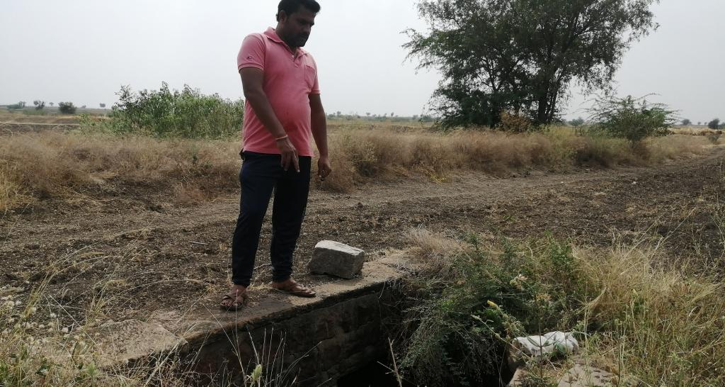 Engineer-turned- farmer Mahantesh Nagaral showing the small well through which water flows into the adjoining field after the soil has soaked up enough moisture. Photo: Akshit Sangomla