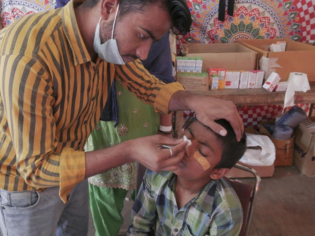 A doctor attends to a minor boy at the medical camp. Cases of insomnia, shock and trauma, urinary tract infections and other minor injuries were reported, according to Dr Wasim Qamar, the association president.