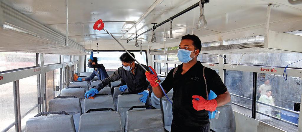 Workers disinfect the interiors of a passenger bus in Ahmedabad, Gujarat