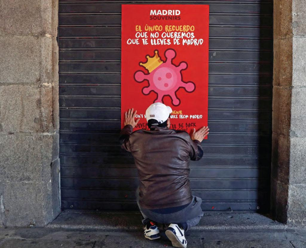 A man, wearing a protective mask, places a poster on the door of a closed shop due to the coronavirus outbreak in central Madrid, Spain