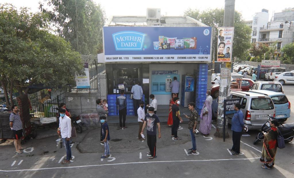 People maintain safe distance while buying milk from a Mother Dairy booth in East Delhi. Circles were drawn outside several grocery shops to encourage people to practise social distancing. The irony of the lockdown played out here — as some streets remained deserted or saw very few people, others were thronged by daily wage workers, including women and children, walking back home.