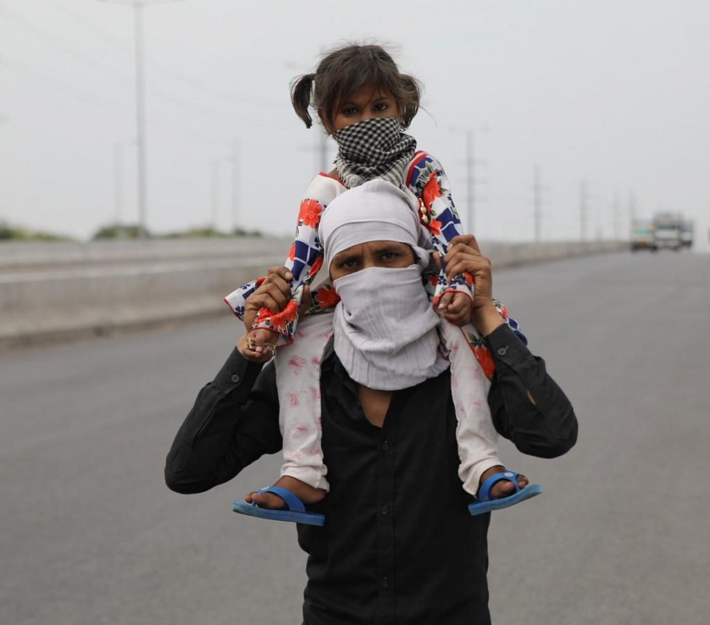 A man carries his daughter on his shoulders. Most labourers said that without work, they could not survive in the city. The Union government received flak for mismanagement that left thousands of migrants in the lurch.