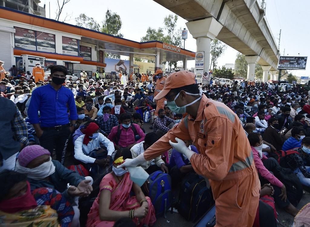 एक एनडीआरएफ कर्मचारी लोगों के हाथ सेनिटाइज करते हुए। फोटो: विकास चौधरी